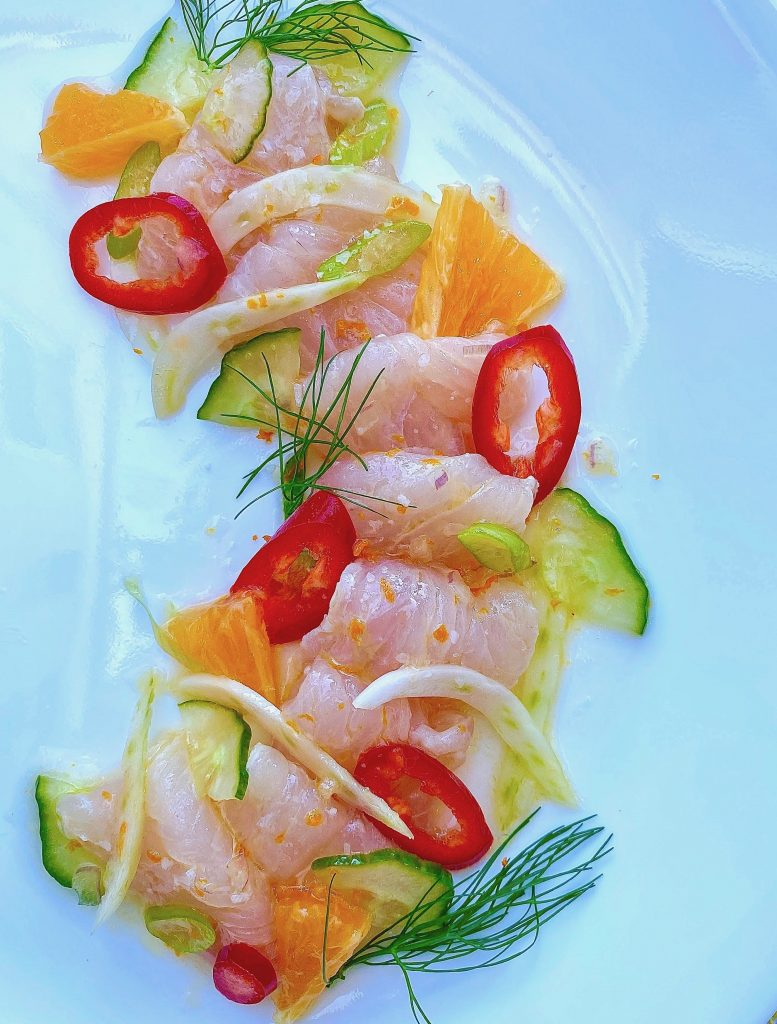 yellowtail fish crude with sliced orange, fennel, and red hot chili peppers